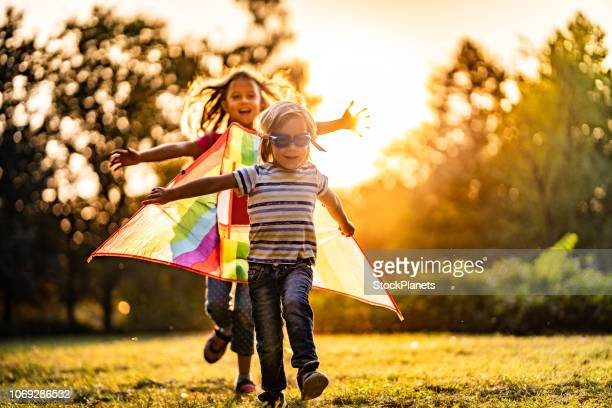 girl running for a little boy pilot - kite toy stock pictures, royalty-free photos & images