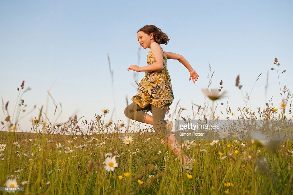 Girl running in field of flowers : Stock Photo