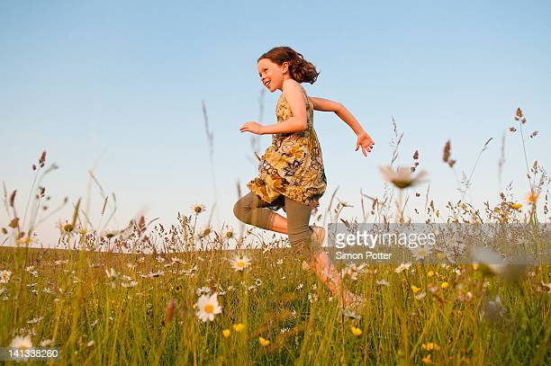 girl running in field of flowers - skipping along stock pictures, royalty-free photos & images