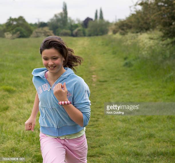 girl (11-13) running in field - bracelet stock pictures, royalty-free photos & images