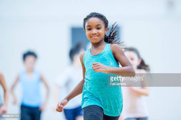 girl running in gym - physical education stock pictures, royalty-free photos & images