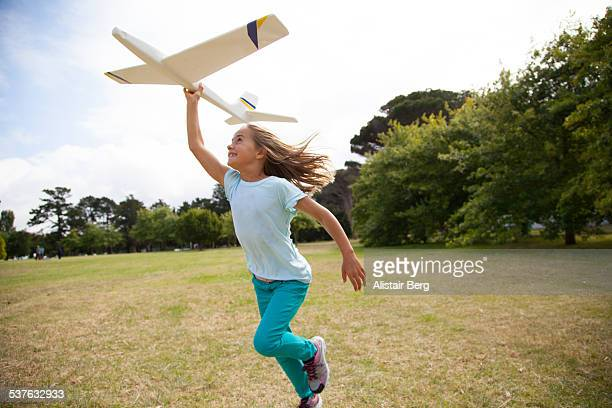 Girl running in park with plane