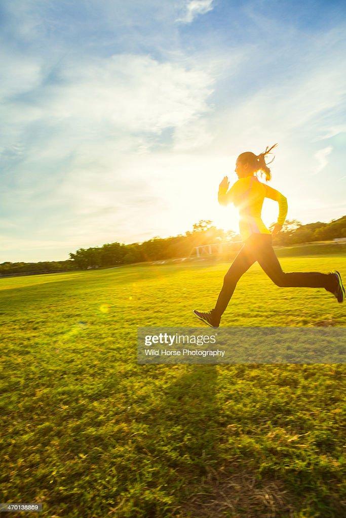 Girl running in sun flare : Stock Photo