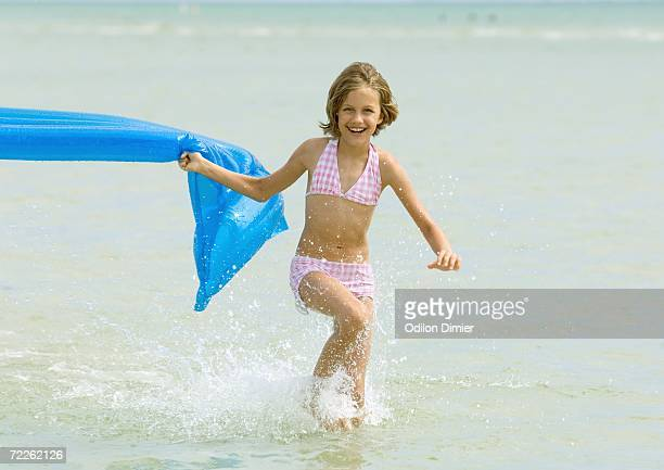 Girl running in surf with air mattress