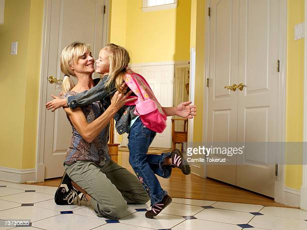 Girl (3-5) running into mother's arms at home, smiling, side view