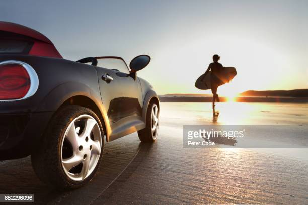 girl running into sea with surfboard, car parked on beach - landfahrzeug stock-fotos und bilder