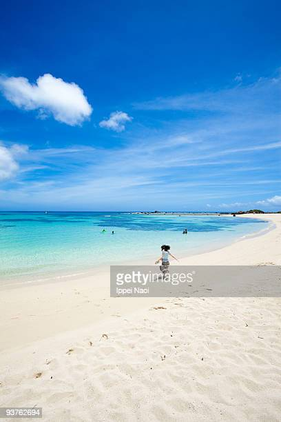 Girl running into the clear blue tropical water