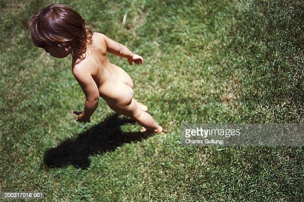 Girl (1-3) running naked on lawn, rear view, elevated view