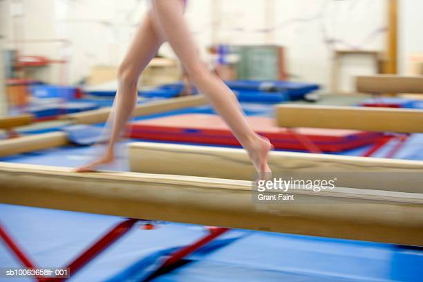 Girl (16-17) running on balance beam, low section (blurred motion)