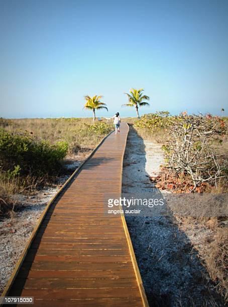 Girl running on beach boardwalk