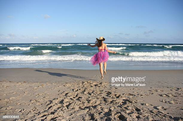 girl running on beach in pink tutu - fauci stock pictures, royalty-free photos & images