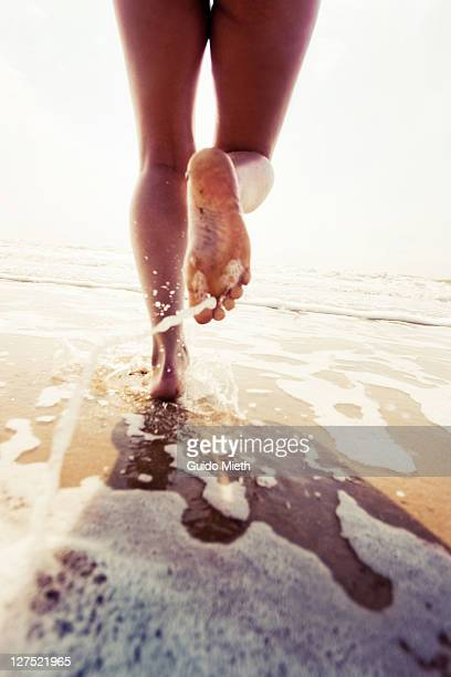 girl running on beach - barefoot soles female stock pictures, royalty-free photos & images
