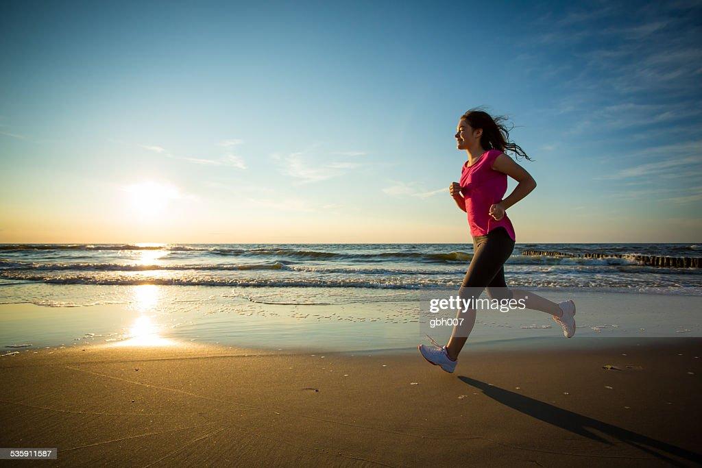 Menina a correr na praia : Foto de stock