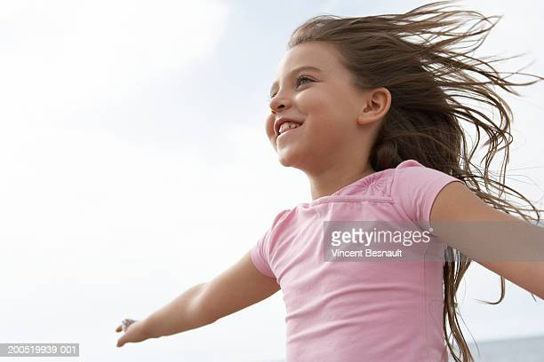 Girl (8-10) running on beach, smiling, low angle view