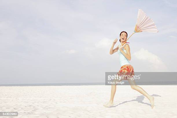 Girl running on beach with umbrella