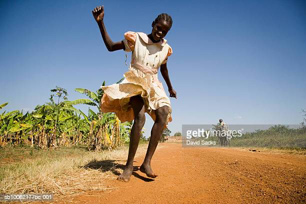 girl (8-9) running on dirt track, smiling, low angle view - developing countries stock pictures, royalty-free photos & images