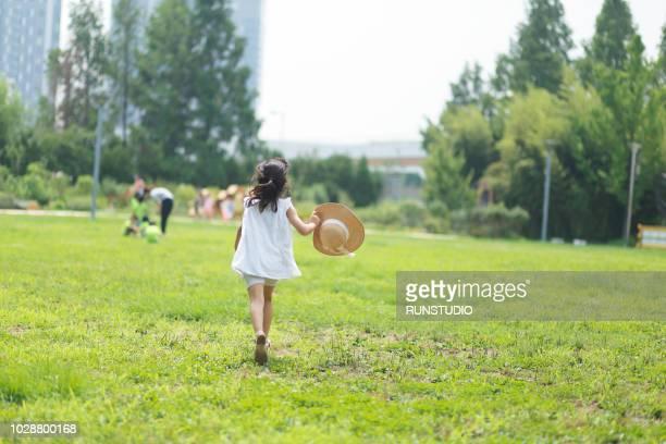 girl running on grassy field at park - シンプルな暮らし ストックフォトと画像