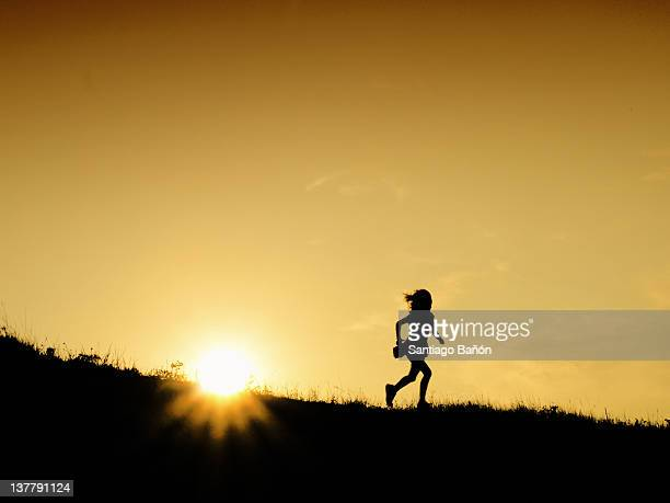 Girl running on hill at sunset