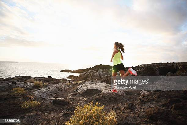 Girl running on rocks near ocean