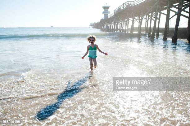girl running on shore at seal beach against sky - seal beach stock pictures, royalty-free photos & images