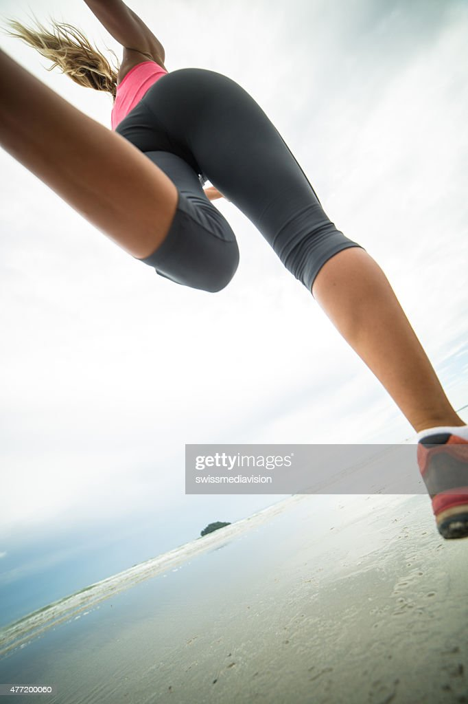 Girl running on the beach-Low angle : Stock Photo