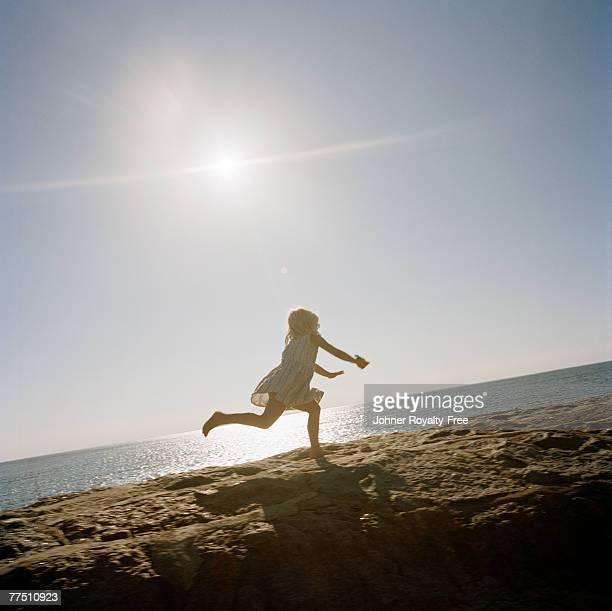 Girl running on the rocks by the sea Oland Sweden.