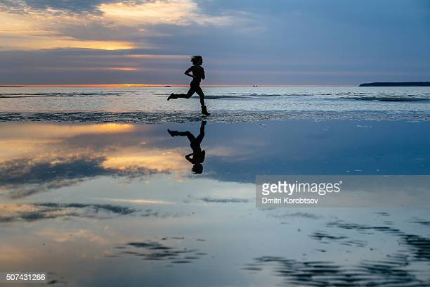 Girl running on the Stroomi beach in Tallinn during the sunset