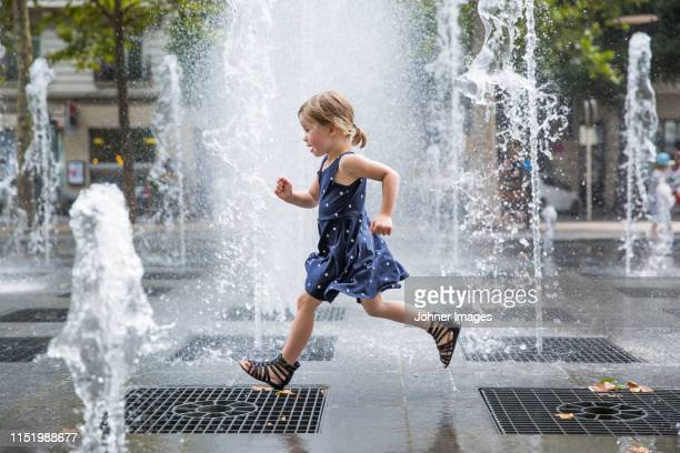 girl running over fountain - fountain stock pictures, royalty-free photos & images