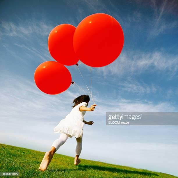 Girl Running Over  Green Landscape Holding Red Balloons