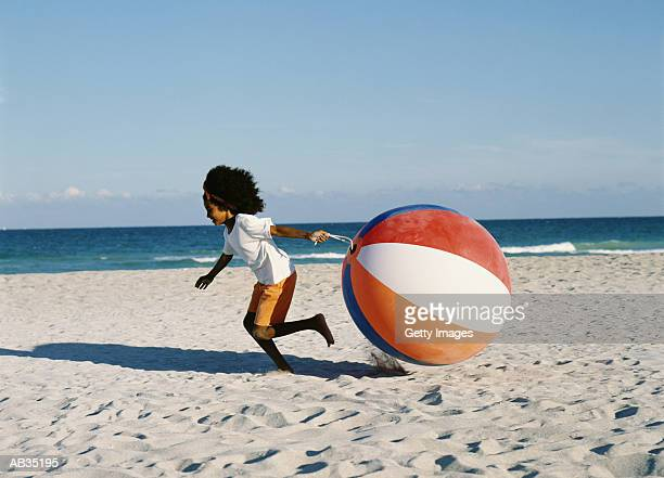Girl (6-8) running pulling beach ball behind her