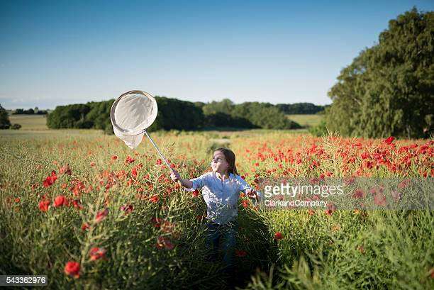 Girl Running Through a Poppy Field Trying To Catch Insects