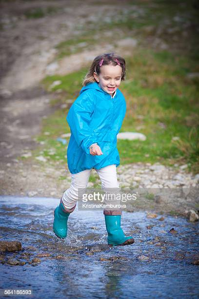Girl running through a puddle