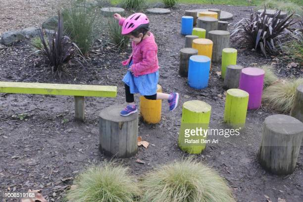 Girl Running Through an Obstacle Course Made from Wooden Poles