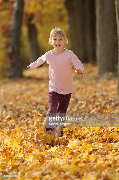 girl (7 years) running through autumn leaves - 6 7 years stock pictures, royalty-free photos & images