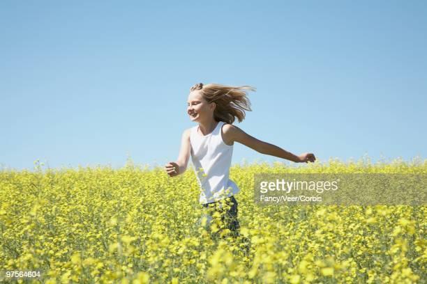 Girl Running Through Field of Canola