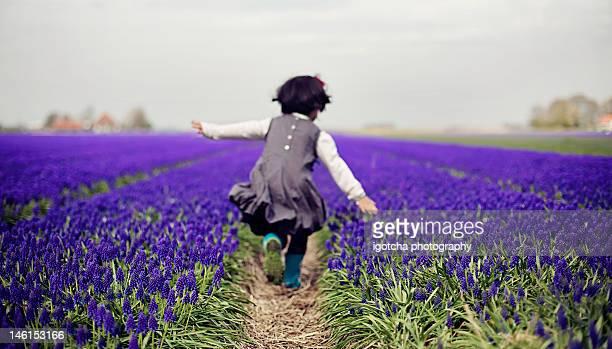 Girl running through field of flowers