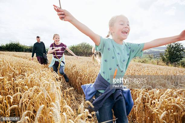 Girl running through field with arms out