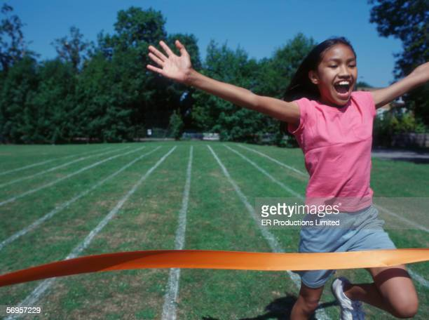 Girl running through finish line at track