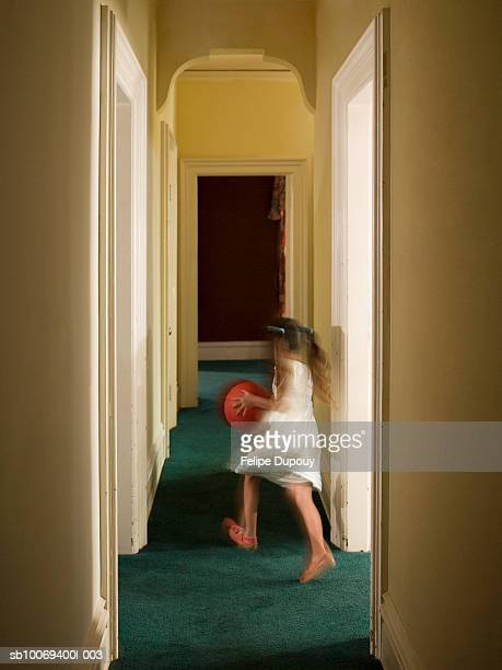 Girl (6-7) running through hallway of house, carrying ball