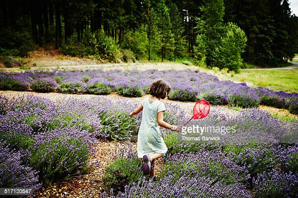 Girl running through lavender with butterfly net