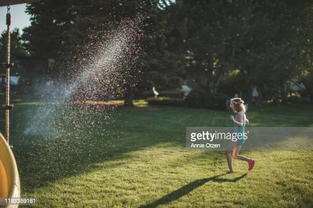 girl running through sprinkler - annie sprinkle stock pictures, royalty-free photos & images