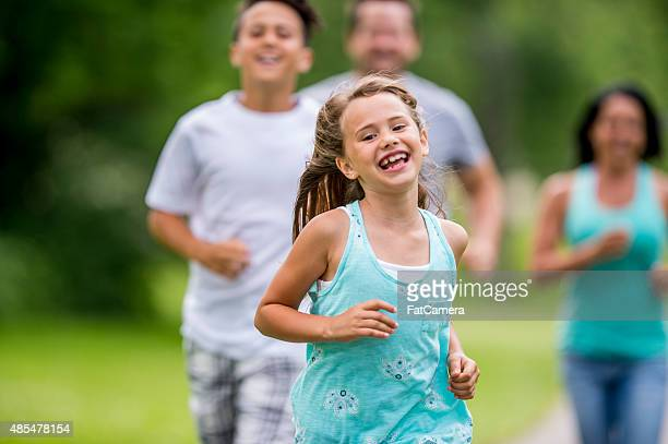 girl running through the park - kids playing tag stock photos and pictures