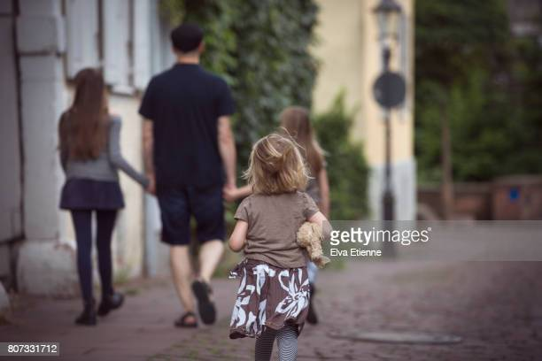 Girl running to catch up with family, walking through a town in Germany