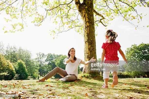 girl running to mother in park - 接近する ストックフォトと画像