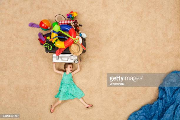 Girl running to the sea, carrying beach equipment on the head