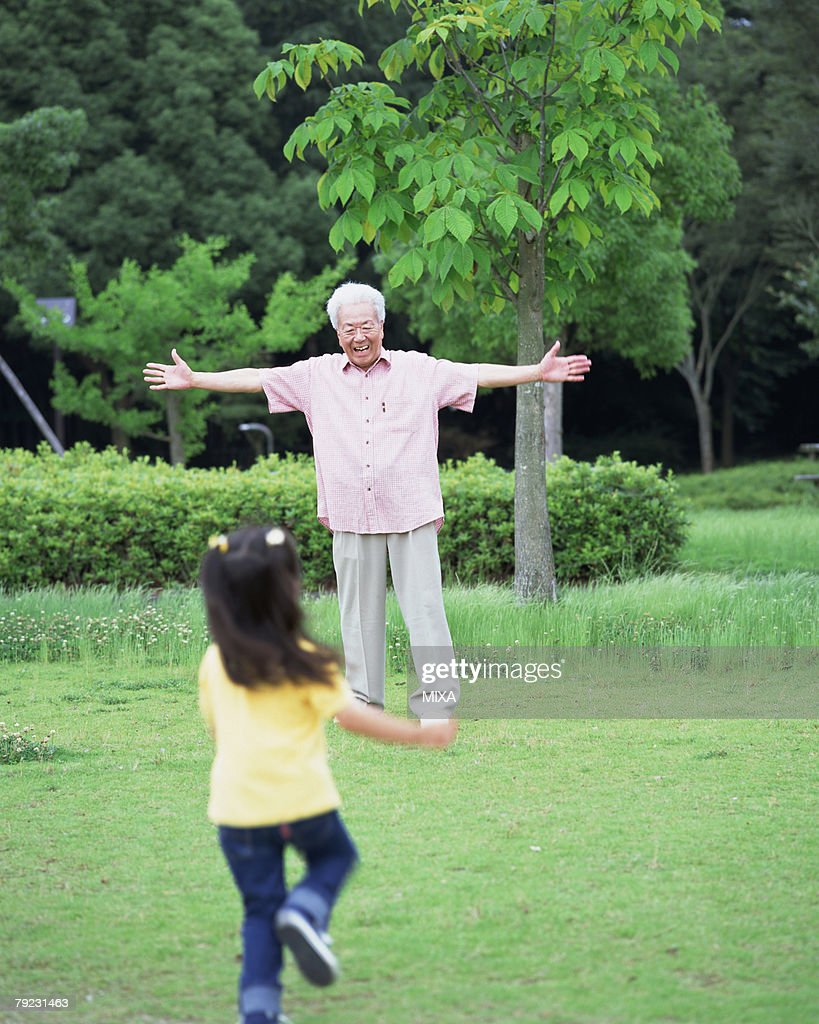 A girl running toward a grand father : Stock Photo