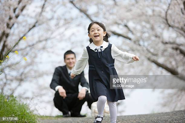 Girl running toward camera, with parents in background