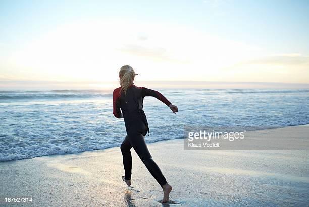 Girl running towards ocean in sunset