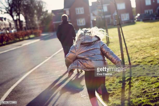 girl running towards teenage boy, on the sidewalk of a residential street in the uk - sister stock photos and pictures