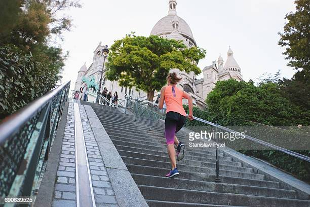 Girl running up stairs near Basilica Sacre Coeur